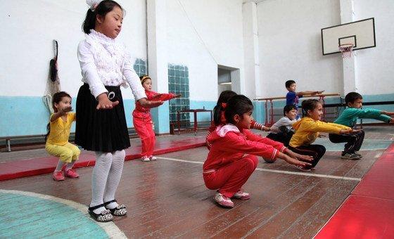 أطفال يقومون بتمارين جسدية في صالة ألعاب رياضية في أوزبكستان، من بينهم طفلة مصابة بمتلازمة داون.