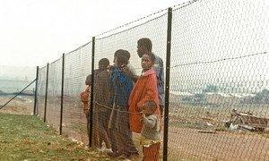 Des enfants derrière un grillage qui les sépare d'une communauté blanche près de Johannesburg, en Afrique du Sud, du temps de l'apartheid. Photo ONU/Pendl