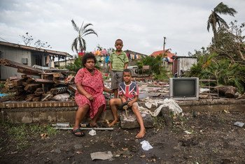 Mereani, 29, and her children sitting on brick wall of what used to be their home in Fiji. Their house was just a few metres from the shoreline and suffered extensive damage during strong storm surges at the height of Cyclone Winston.