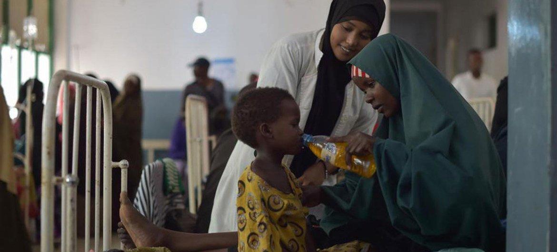 Une mère donne à sa fille un verre de sels réhydratants dans un hôpital de Mogadiscio, en Somalie. Photo ONU/Tobin Jones