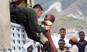 A UN peacekeeper helps a child aboard a truck during the relocation of residents of a camp for displaced persons.