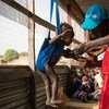 UNICEF Nutrition Officer Judy Jurua Michael (centre) weighs 13-month-old Alakaii during a malnutrition screening at Gabat Center, a UNICEF-supported Outpatient Therapeutic Programme in Aweil, South Sudan, Monday 13 March 2017.