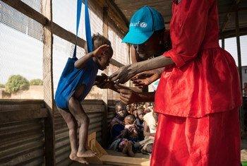 مسؤولة التغذية في اليونيسف جودي جوروا مايكل تزن ألكايي البالغ من العمر 13 شهرا أثناء فحص سوء التغذية في مركز غابات، وهو برنامج علاجي معتمد من اليونيسف في أويل، جنوب السودان، مارس 2017. المصدر: اليونيسف / ماكنزي نولز-كورسين