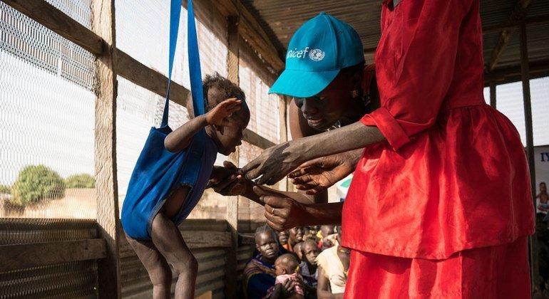 Un trabajador de UNICEF pesa a Alakaii, un niños de trece meses, en un centro de Sudán del Sur para combatir la malnutrición.