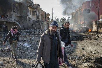 Семья выбирается из своего разрушенного дома спустя несколько минут после того, как террорист-самоубийца ИГИЛ взорвал автомобиль на улице рядом с их домом в городе Мосул в Ираке