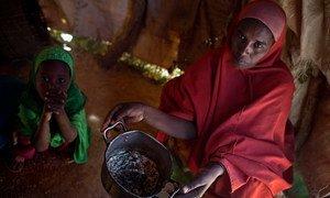 Une mère tient un ustensile de cuisine vide chez elle, dans un village près de la ville d'Ainabo, en Somalie, le jeudi 9 mars 2017. Photo UNICEF/Kate Holt