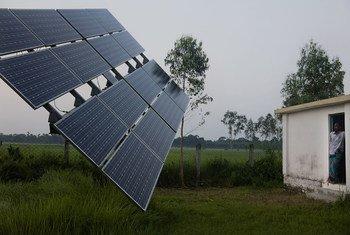 Un encargado de las bombas de agua de Nusra trabaja cerca de paneles solares. Nusra es una ONG que proporciona herramientas de riego impulsado por energía solar a los agricultores y sistemas solares domésticos en Rohertek, Bangladesh.