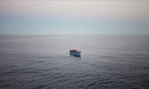 An overloaded boat of refugees and migrants trying to reach Europe, as seen from the deck of an Italian Coastguard ship, in the Mediterranean Sea. (file photo)