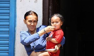 A grandmother feeds her two year old granddaughter in Naubise, Dhading. Nepal