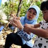 A volunteer community health worker shows a child how to wash her hands properly with soap, at an outdoor tap at the local community health post in Klaten District, Central Java Province, Indonesia.