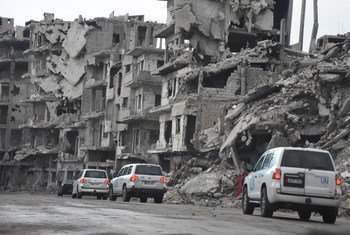 A UN convoy drives past destroyed buildings in the old city of Homs, Syria. March 2017.