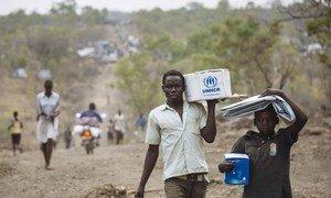 Des réfugiés sud-soudanais avec des articles de secours dans le site pour réfugiés de Bidibidi, en Ouganda. Photo HCR/David Azia