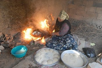 A woman prepares bread at her home in Faqua village, Jordan for sale in the local market. Since her husband passed away in 2002, she has had to take care of her family of nine children. With her small business of bread, cheese and Jabeen (dry yogurt) she earns enough to survive.