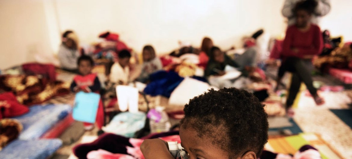 A child stands in a room where women and children sleep on old mattresses laid on the floor at a detention centre in Libya.