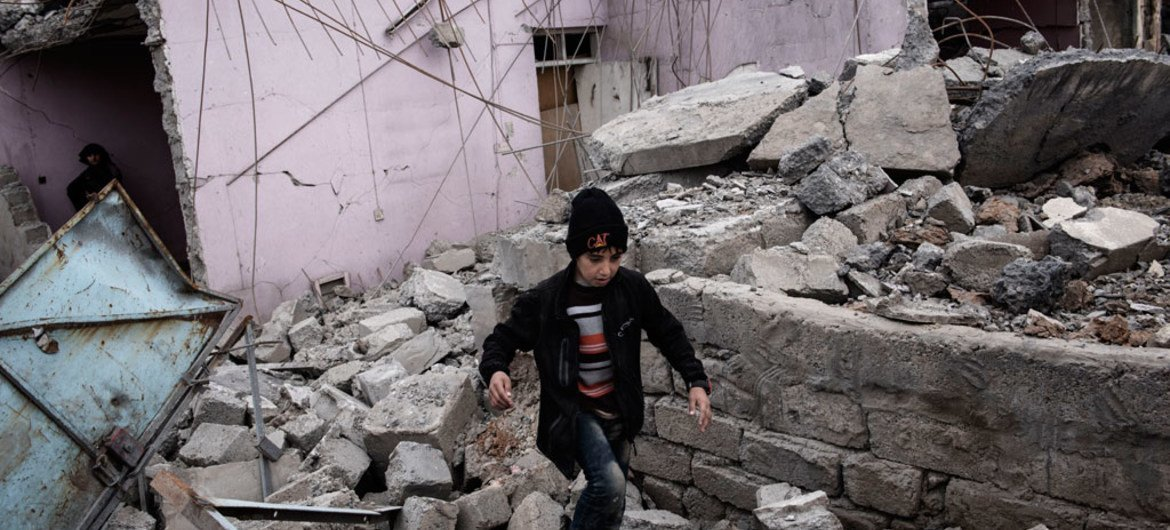A child walks through the rubble of a building which was destroyed in an airstrike, during fighting between Iraqi security forces and ISIL in western Mosul. 11 March 2017.