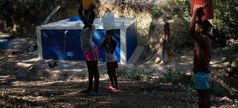 مواطنون يملأون أوعيتهم بالماء من مشروع توزيع ببلدة تبعد ساعة عن العاصمة بورت أو برنس.