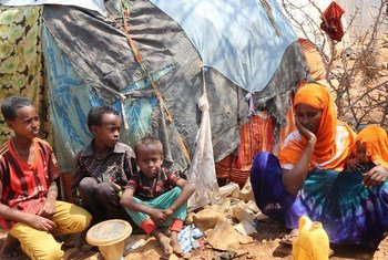أطفال نازحون مع أمهم في مخيم للنازحين داخليا في بايدوا بالصومال.