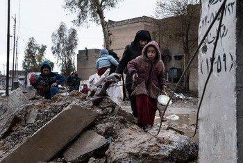 Une famille déplacée par les combats entre l'EIIL et les forces de sécurité iraquiennes porte ses affaires à travers le quartier détruit d'Al Mamum, près de Mossoul, en Iraq, en avril 2017.