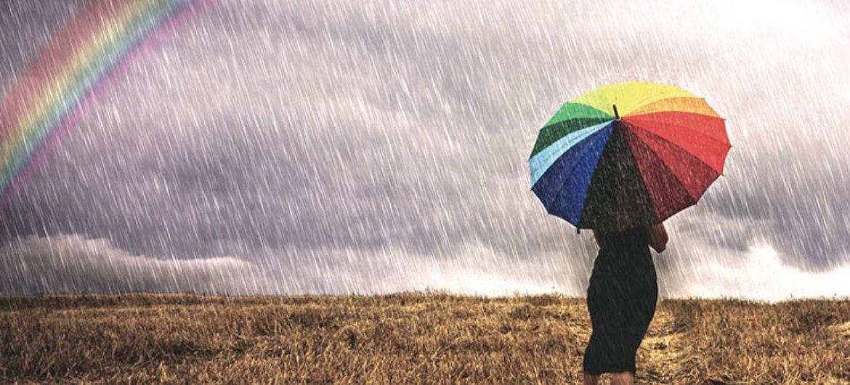 Une femme avec un parapluie marche sous la pluie dans un champ