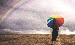 A woman with an umbrella walks in the rain in a field. To the left is a rainbow.