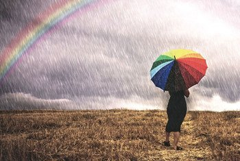 A woman with an umbrella walks in the rain in a field. To the left is a rainbow. Photo: WMO