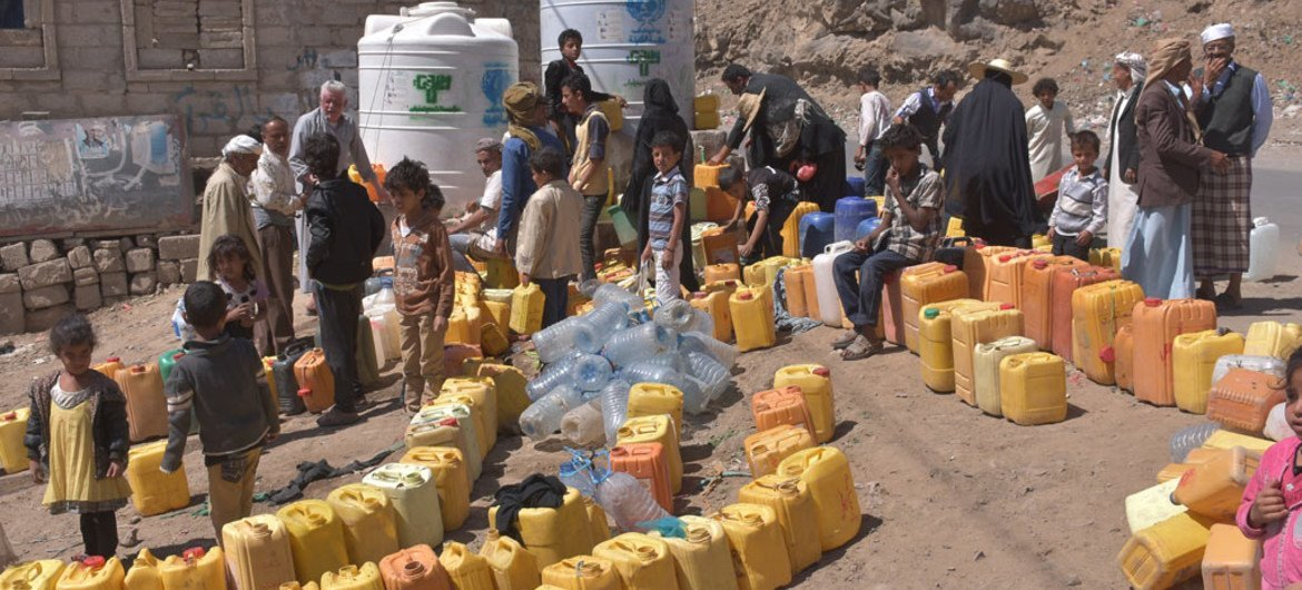 People queue to fill containers with water from a tank provided by UNICEF in Sana'a, Yemen. Some 14.5 million people in the country have no access to safe drinking water and adequate sanitation.