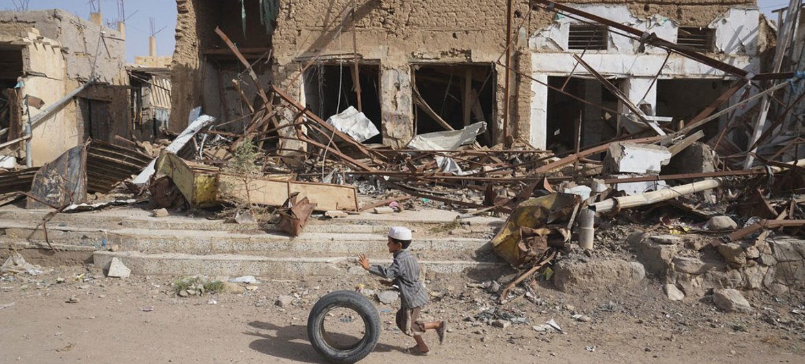 A young boy runs with his tyre past buildings damaged by airstrikes in Sa'ada Old Town, Yemen. Up until August 2015, this area was the home of Sa'ada's oldest market with thousands of people selling vegetables, spices and fabrics in stores and street stalls.