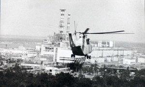 Un hélicoptère s'approche de la centrale nucléaire de Tchernobyl pour vérifier les dommages causés au réacteur nucléaire en avril 1986. Photo ONU/AIEA