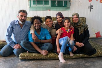 UNICEF Advocate Ishmael Beah with a displaced family at the Za'atari refugee camp in Jordan.