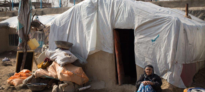 Une femme âgée à l'extérieur de son habitat improvisé en Afghanistan.