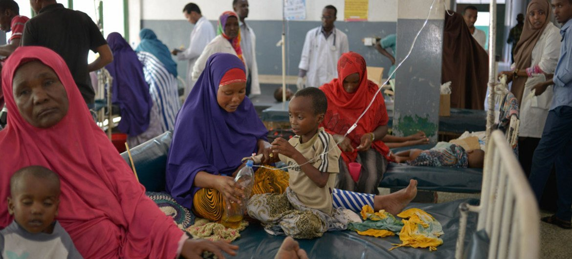 Malnourished children, many of them suffering from diarrhea, lie on beds in Banadir hospital in Mogadishu, Somalia, while their parents and hospital staff tend to them.