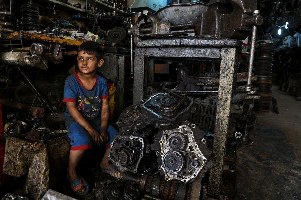 国际劳工组织敦促采取行动,确保社会保护能够惠及所有儿童,保护他们免受贫困,就像6岁的穆斯塔法,他在巴格达的工业区与父亲一起工作。