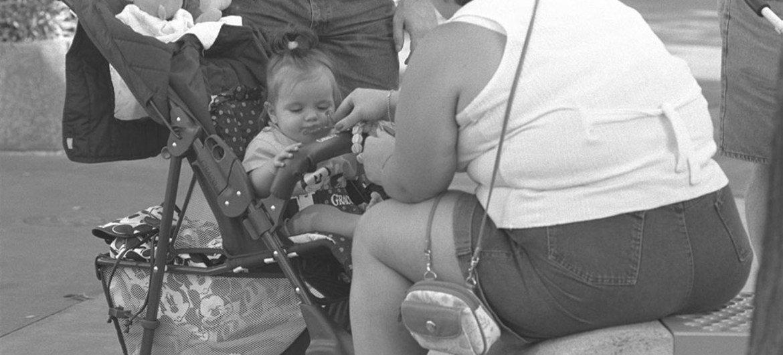 Un bébé assis dans une poussette est nourri par sa mère dans le parc d'attractions Disney World à Orlando, en Floride (1997). Photo UNICEF/Toutounji