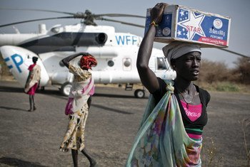 Des femmes transportent des vivres d'urgence depuis un hélicoptère du Programme alimentaire mondial (PAM) qui a atterri à Thanyang, au Soudan du Sud.