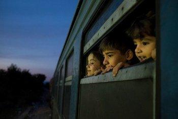在前南斯拉夫的马其顿共和国,三名儿童从一辆载满叙利亚、阿富汗和伊拉克难民和移民的火车窗口向外望去。
