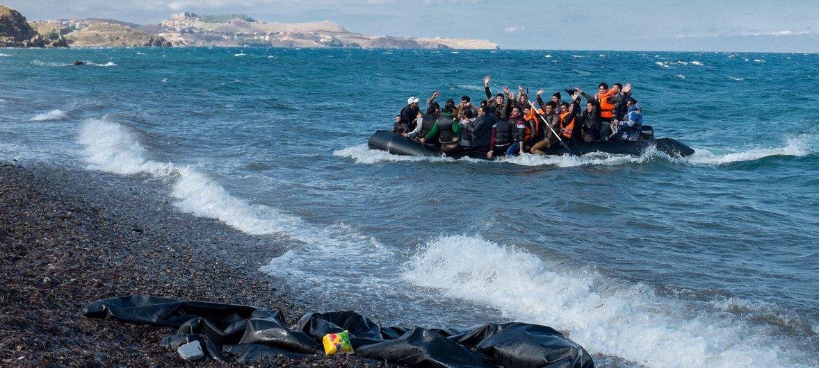 Des réfugiés rient et saluent alors que le zodiac dans lequel ils se trouvent s'approche du rivage, près du village de Skala Eressos, sur l'île de Lesbos, en Grèce.