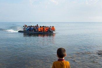 Un niño observa desde la costa una embarcación de refugiados acercándose a la isla de Lesbos, en Grecia. Foto: UNICEF/Ashley Gilbertson VII