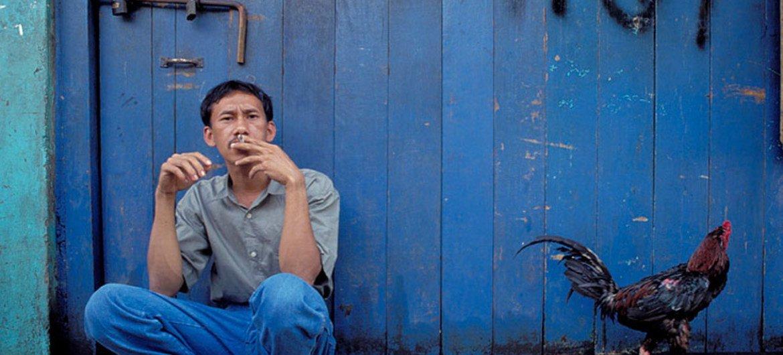 Un hombre fuma un cigarrillo en la puerta de su casa en Indonesia. Foto: Banco Mundial/Curt Carnemark