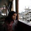 一位居住在加沙的巴勒斯坦女孩在遭到破坏的家中望着窗外的残垣断壁。