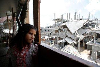 Une fille palestinienne dans la maison partiellement détruite de sa famille, regarde à l'extérieur le quartier détruit de Shejaiya dans la ville de Gaza.