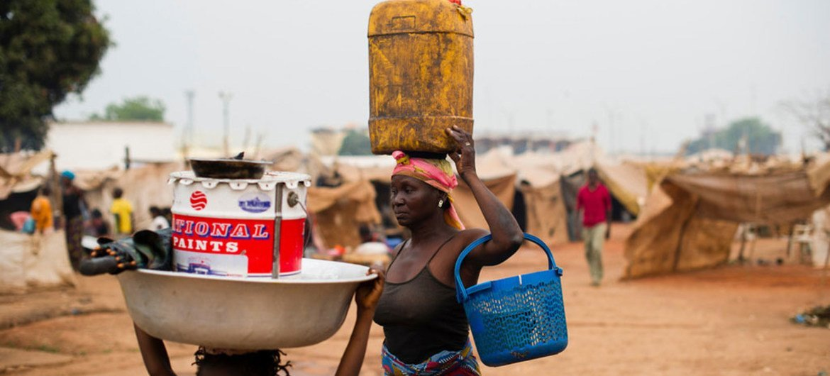 Displaced people carry belongings through the M'Poko airport camp in Bangui, Central African Republic.