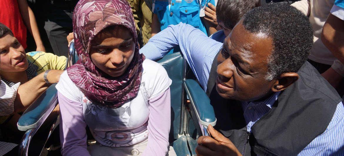 UNFPA Executive Director, Dr. Babatunde Osotimehin, with a Syrian teenage girl with special needs at the Nizip Camp in Turkey.
