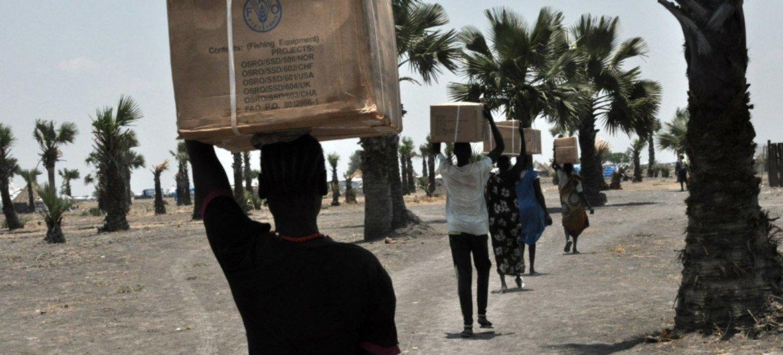 Des habitants transportent des fournitures humanitaires livrées dans la ville de Mayendit, au Soudan du Sud. Photo OCHA/Guiomar Pau Sole.
