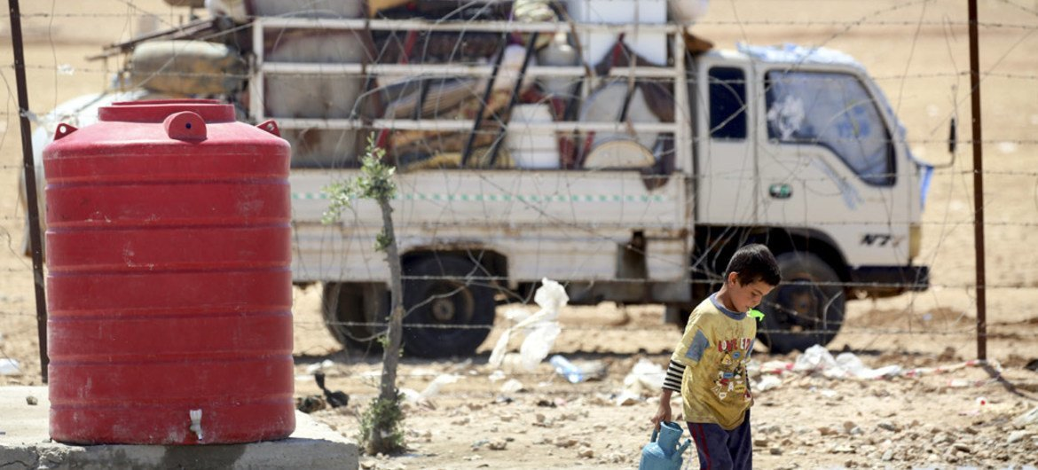 In the makeshift camp at Ain Issa, 50 km north of the Raqqa in Syria, a boy carries a jerrycan filled with water.