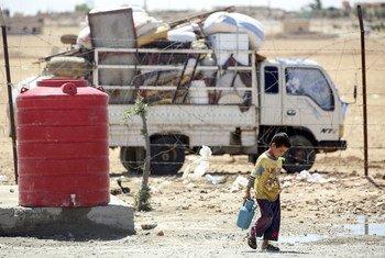 叙利亚拉卡以北的一处简易难民营,一名男孩在打水。