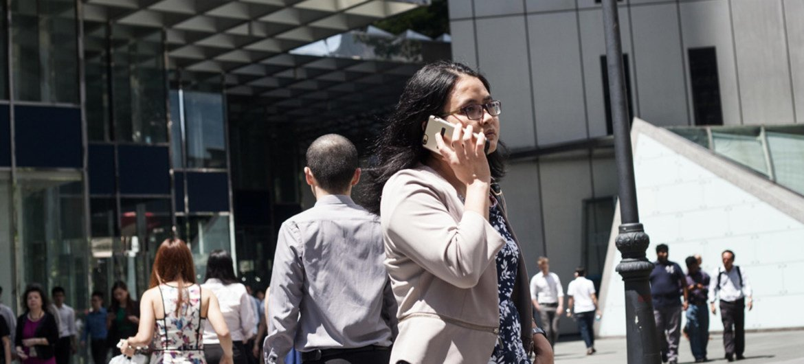 A woman walks speaks on the phone as she walks to work in Singapore.