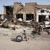 也门萨达老城,一名男童滚着轮胎从已成废墟的房屋跟前经过。