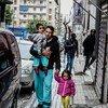 一名阿富汗难民带着自己的两个孩子从希腊雅典一家难民学习中心门外经过。