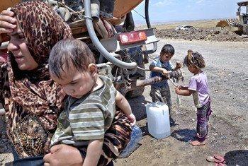 Una mujer iraquí y sus hijos, desplazados internos de Mosul, junto a un camión de agua. Foto: ACNUR / S. Baldwin