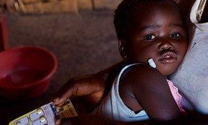 Une fille de deux ans, dans les bras de sa mère, reçoit un médicament pour traiter le paludisme dans une clinique communautaire du district rural de Kasungu, au Malawi.